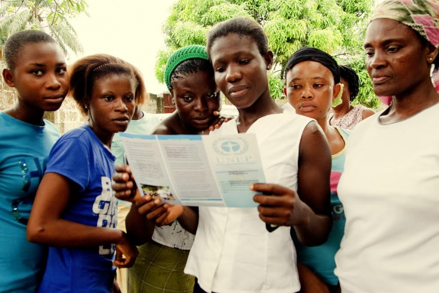 Six African young women standing while reading a UNEP leaflet on the hands of one of them